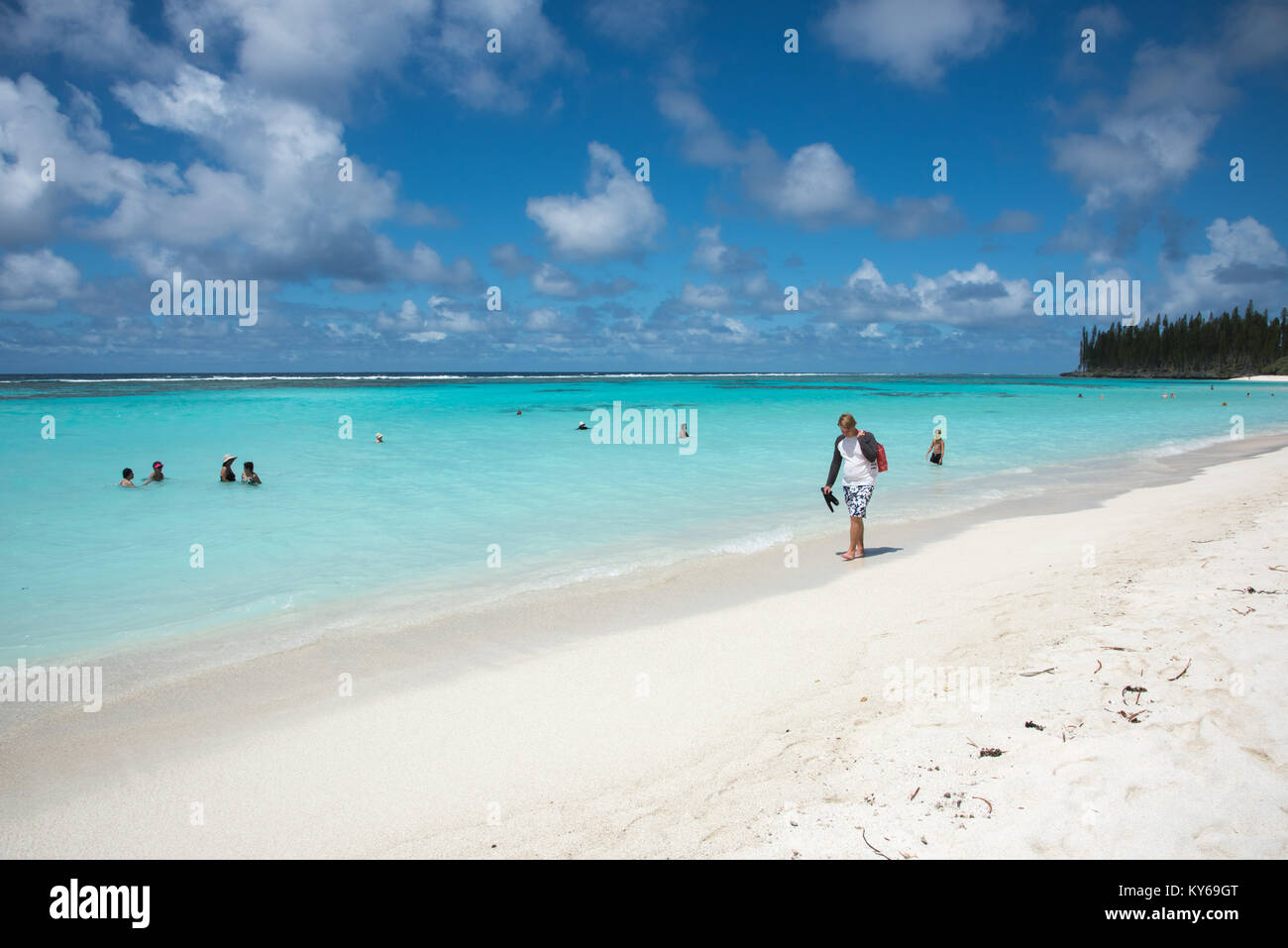TADINE,MARE,NEW CALEDONIA-DECEMBER 3,2016: Tourist walking shoreline with other swimming at Yejele Beach in Mare, - Stock Image