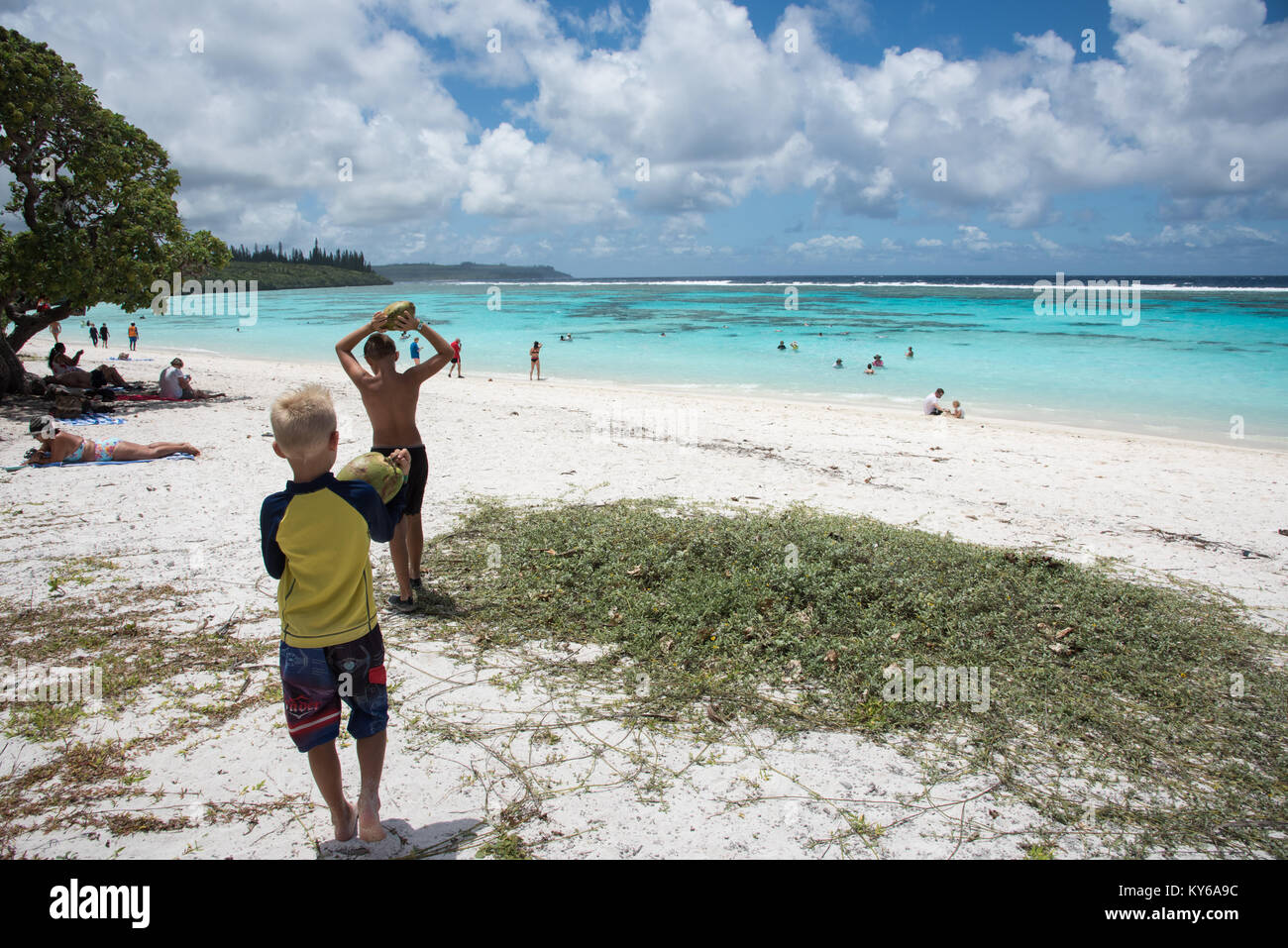 TADINE,MARE,NEW CALEDONIA-DECEMBER 3,2016: Kids collecting coconuts and tourists swimming at Yejele Beach in Mare, - Stock Image