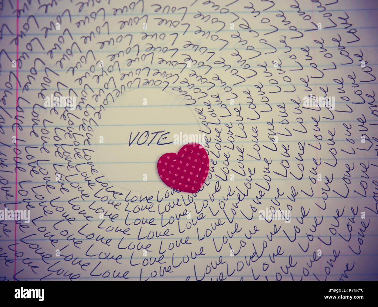 the word love written on a lined piece of school paper in ink with a vignette and a circle of love (focus on the - Stock Image