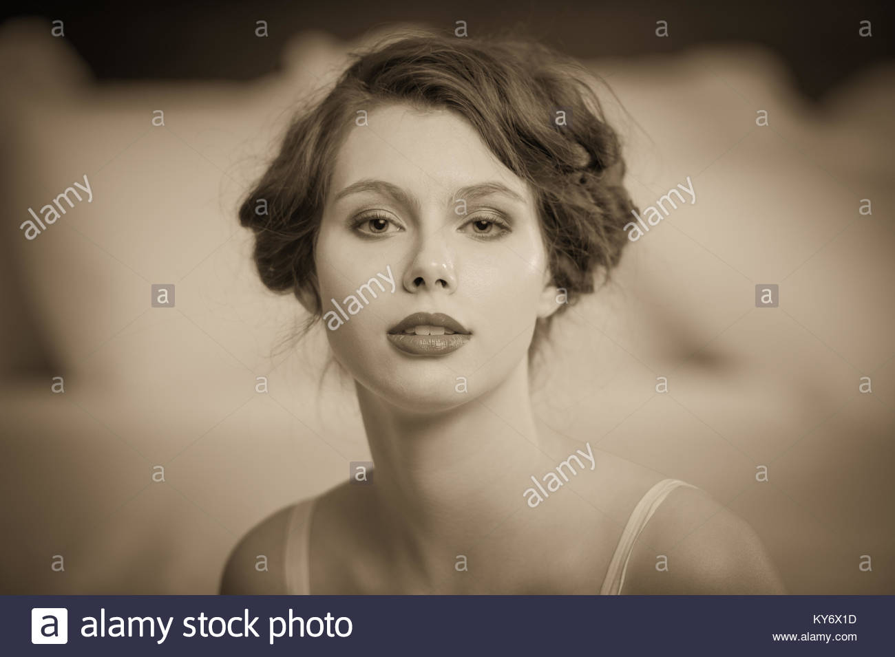 1920's style hair do on a woman facing the camera in sepia tone. - Stock Image