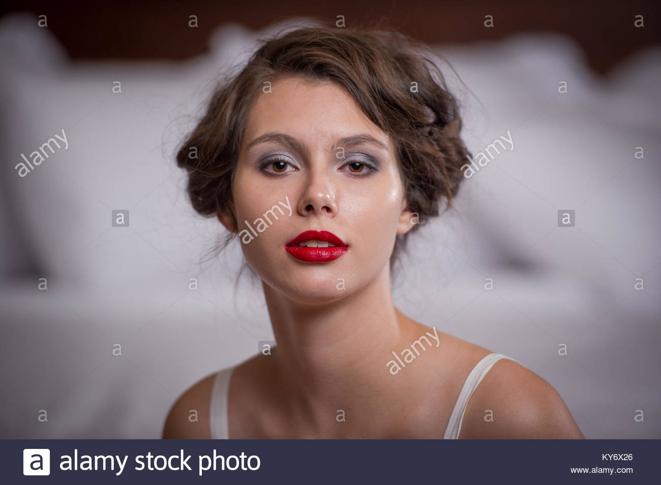portrait of a young woman with a 1920's style hair do looking into the camera. - Stock Image