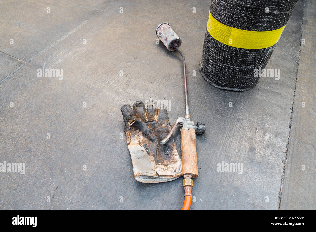 Roll of bituminous sheath, propane torch and glove resting on a bituminous membrane already laid - Stock Image