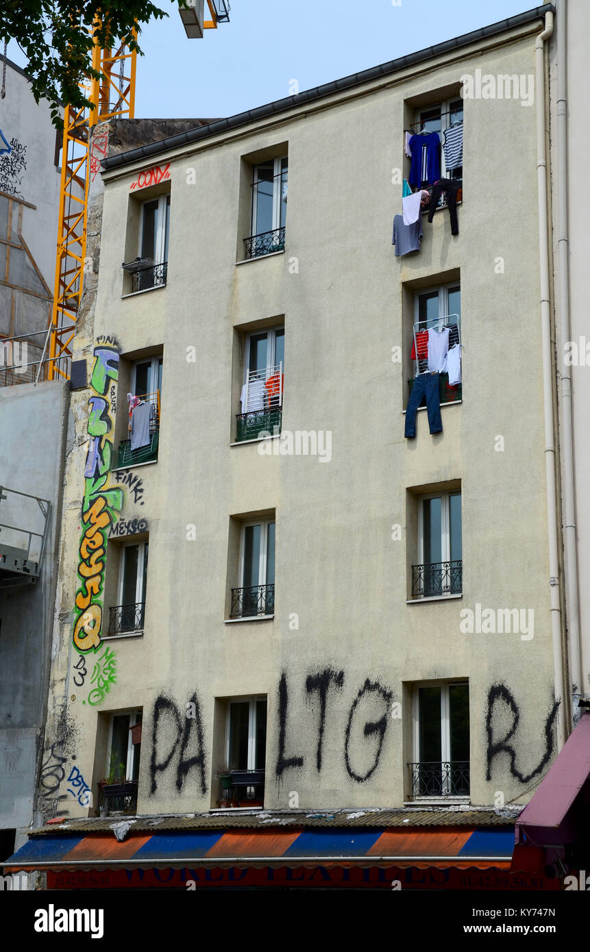 Old building in Paris, France with graffiti and washing handing from windows. Washing fallen down to awning. - Stock Image