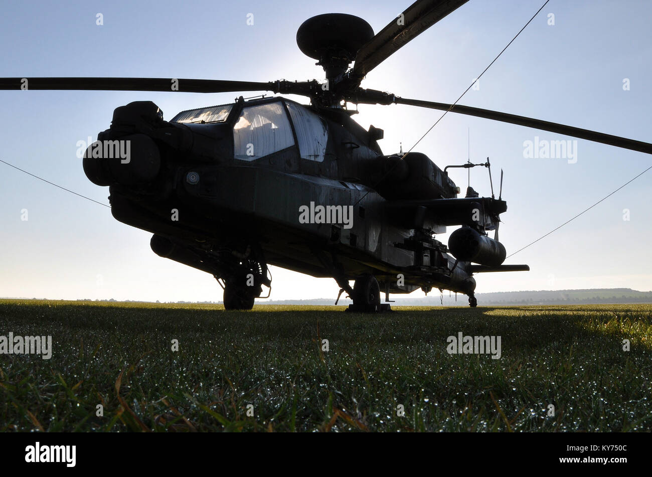 British Army Apache gunship sitting on grass with dew early in the morning. Westland AH-64 Longbow Apache. Space - Stock Image