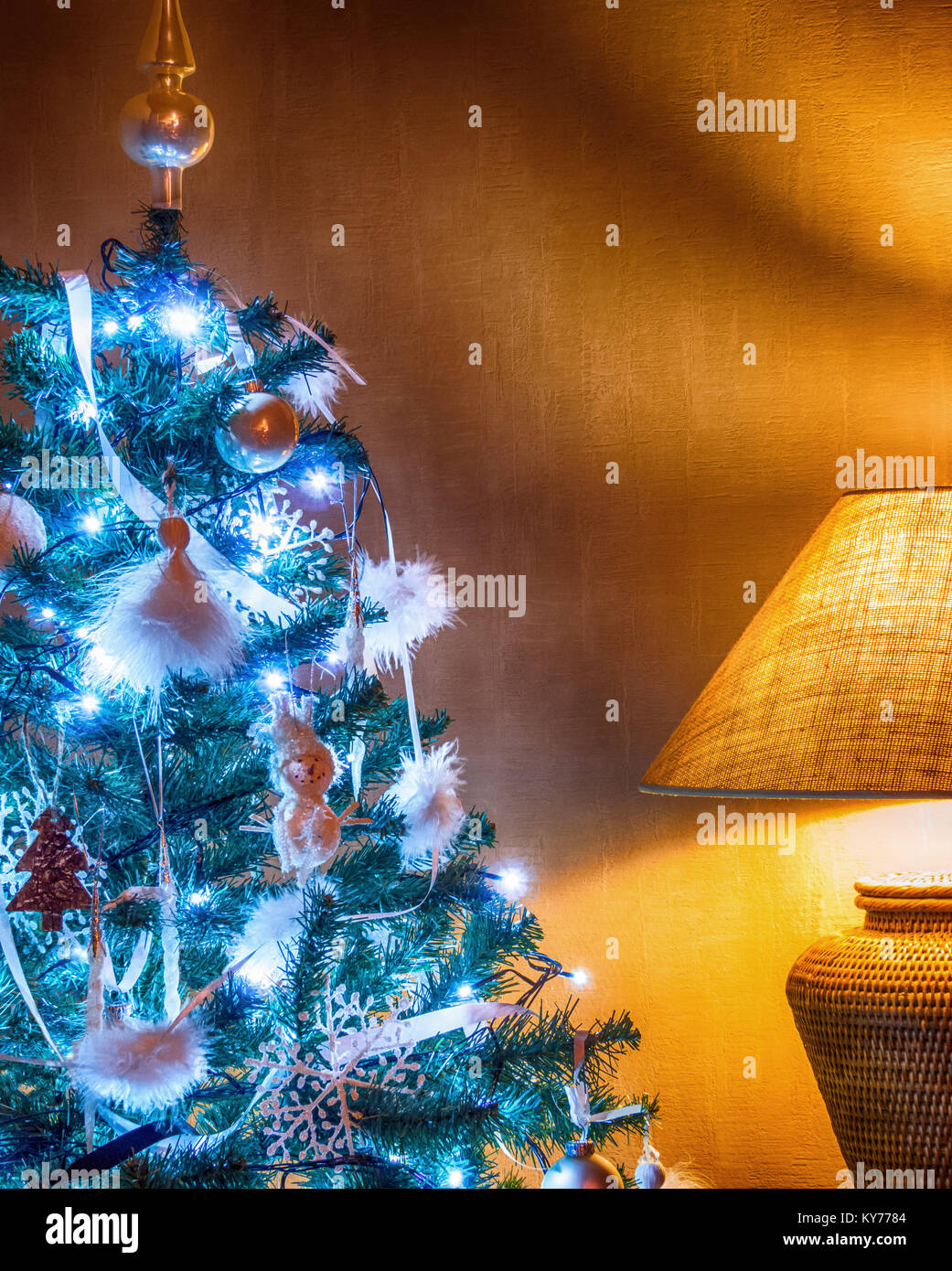 decorated christmas tree with blue lights and yellow table lamp against KY7784