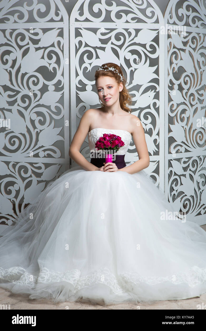 beautiful red hair young woman in white wedding gown with wide dark ...