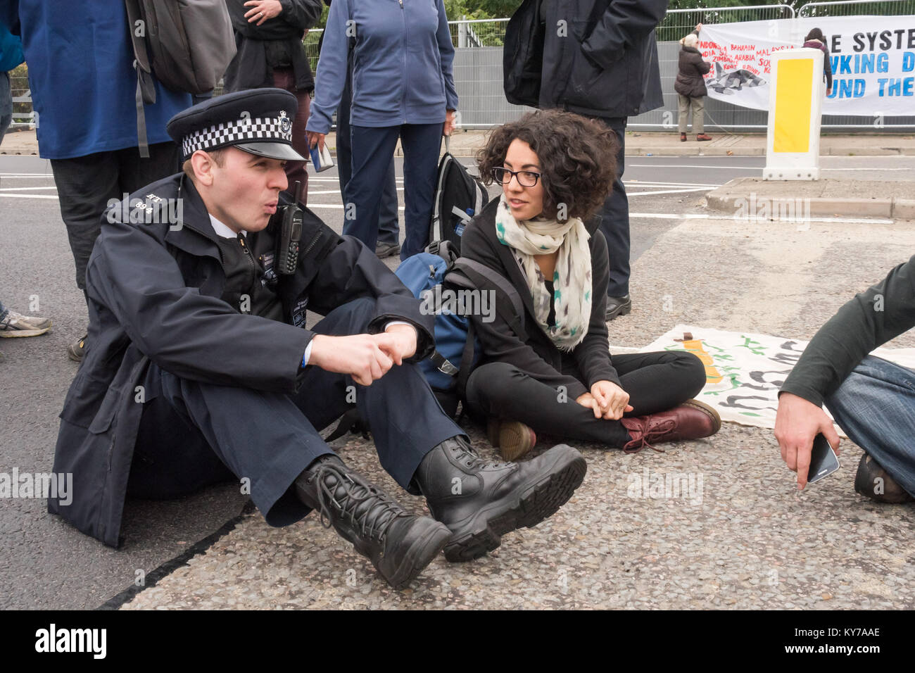Police talk to peace campaigners blocking the road leading to the the ExCeL centre where the DSEi Arms Fair begins Stock Photo