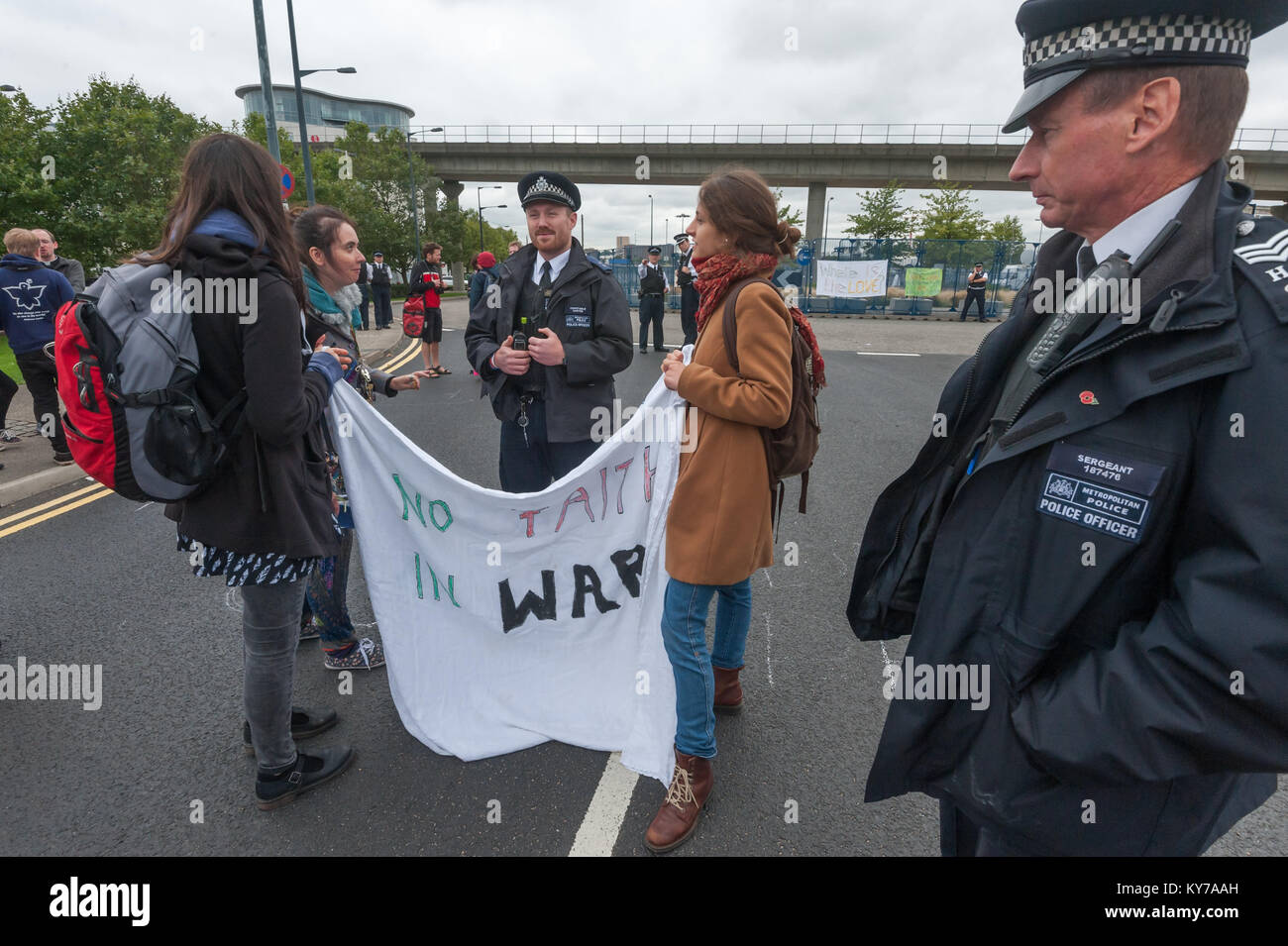 Police talk to peace campaigners holding a banner 'No Faith In War' blocking the road leading to the the ExCeL centre Stock Photo