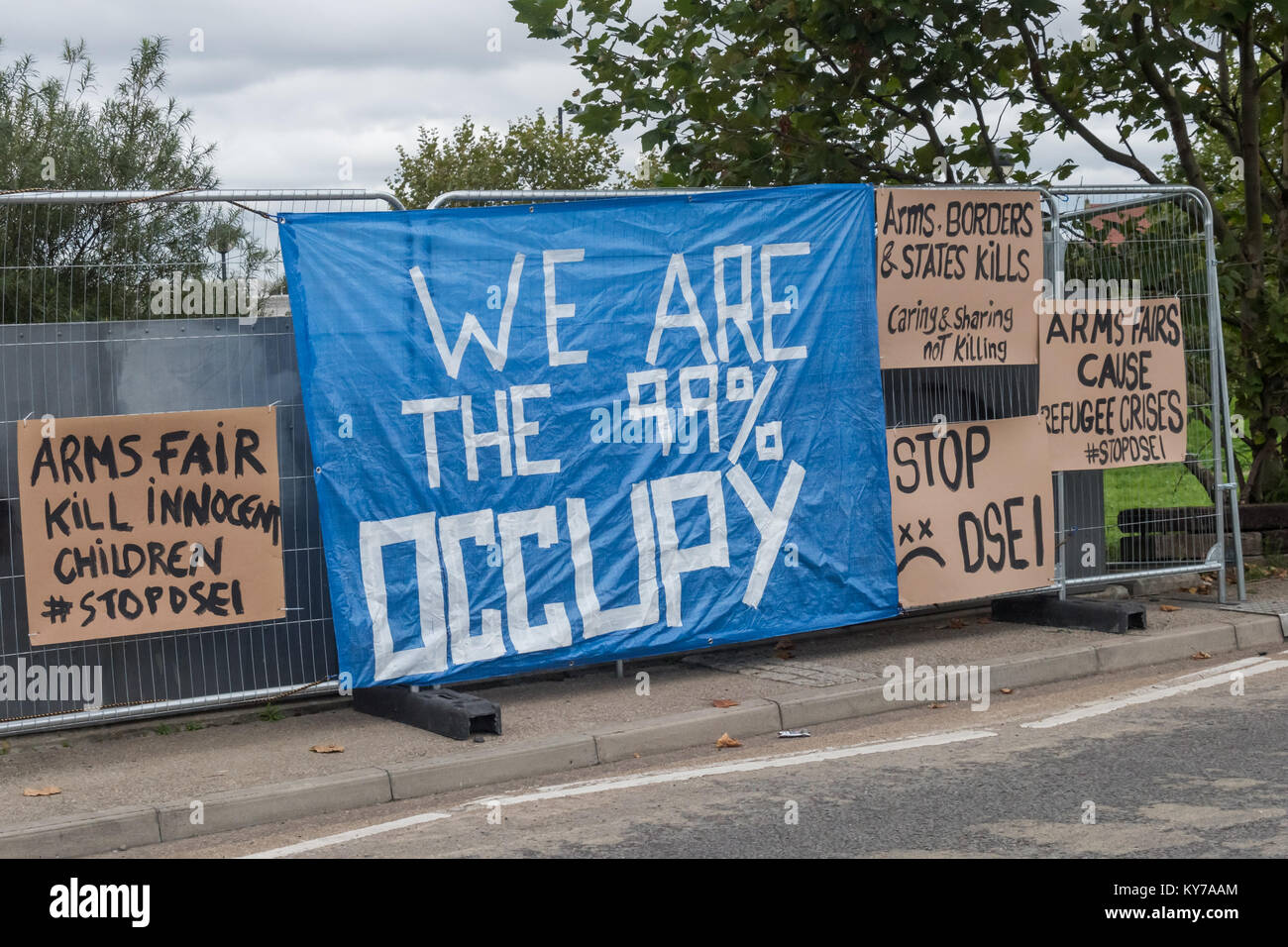 Posters and banners against the arms fair on fences at the side of the road leading to the the ExCeL centre where Stock Photo