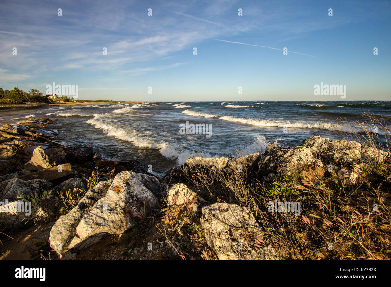 Scenic Rocky Coast. Waves crash on the rocky coast of Lake Superior on a sunny summer afternoon. - Stock Image