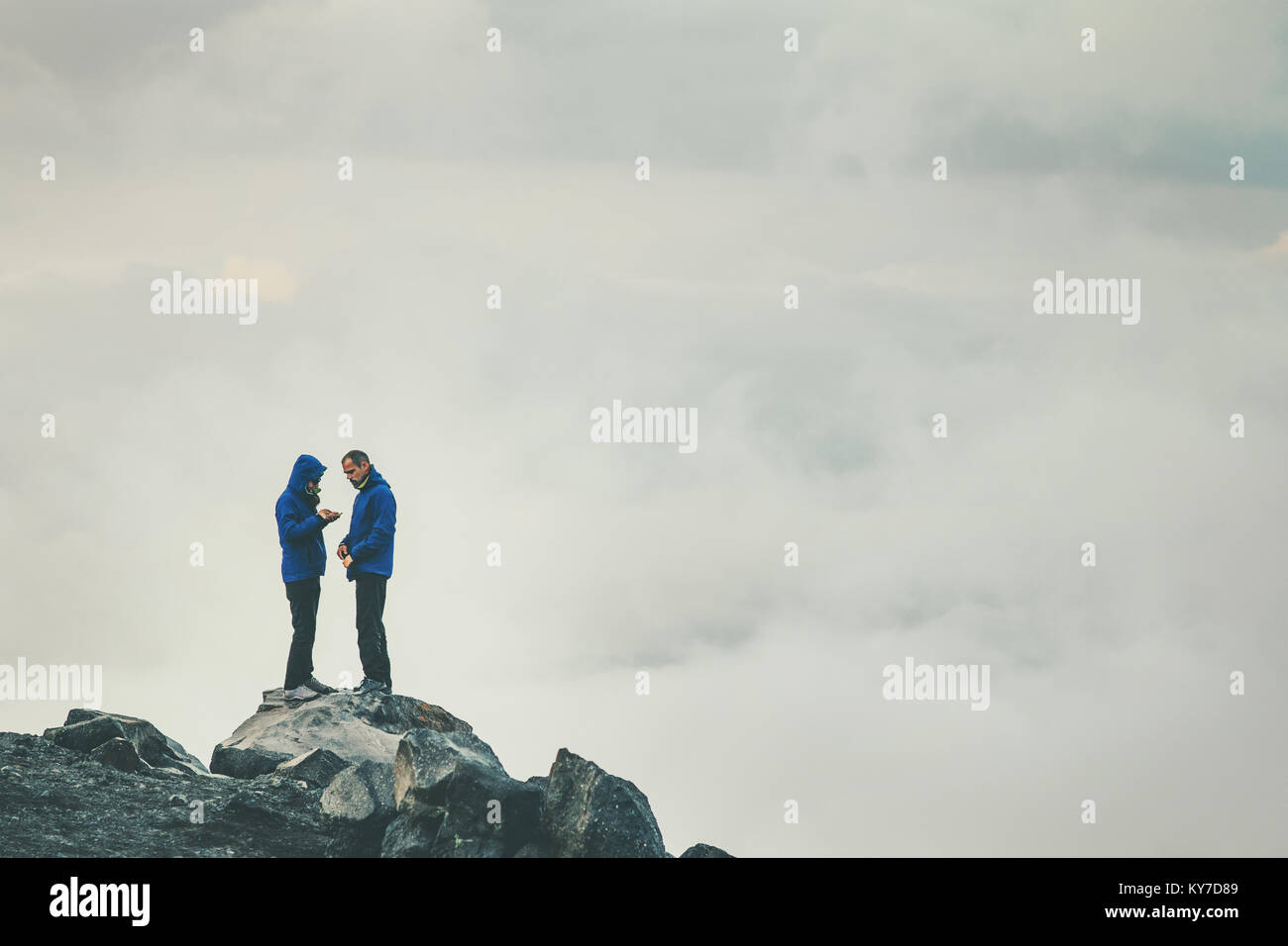 Couple Travelers in love standing on cliff together enjoying cloudy foggy mountains landscape Travel Lifestyle freedom - Stock Image
