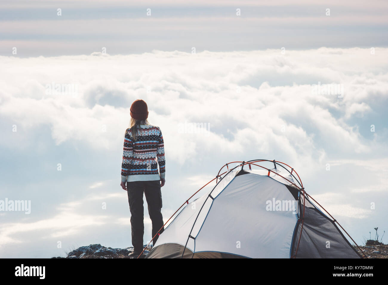 Woman on mountain cliff alone foggy clouds landscape on background Travel Lifestyle concept adventure vacations - Stock Image
