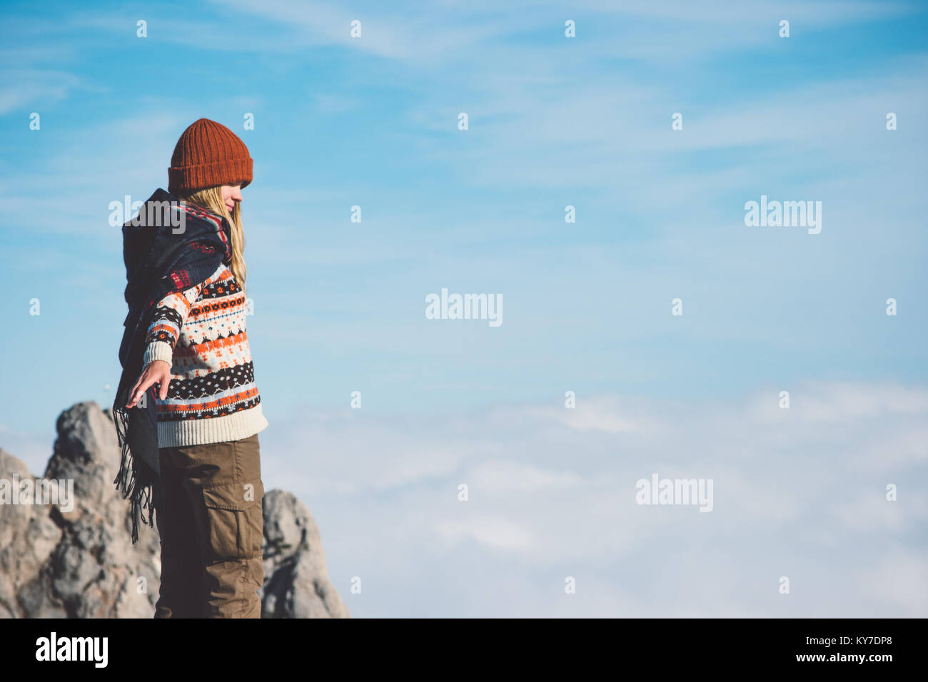 Woman on mountain summit sky clouds on background Travel Lifestyle concept adventure vacations outdoor wearing scarf - Stock Image