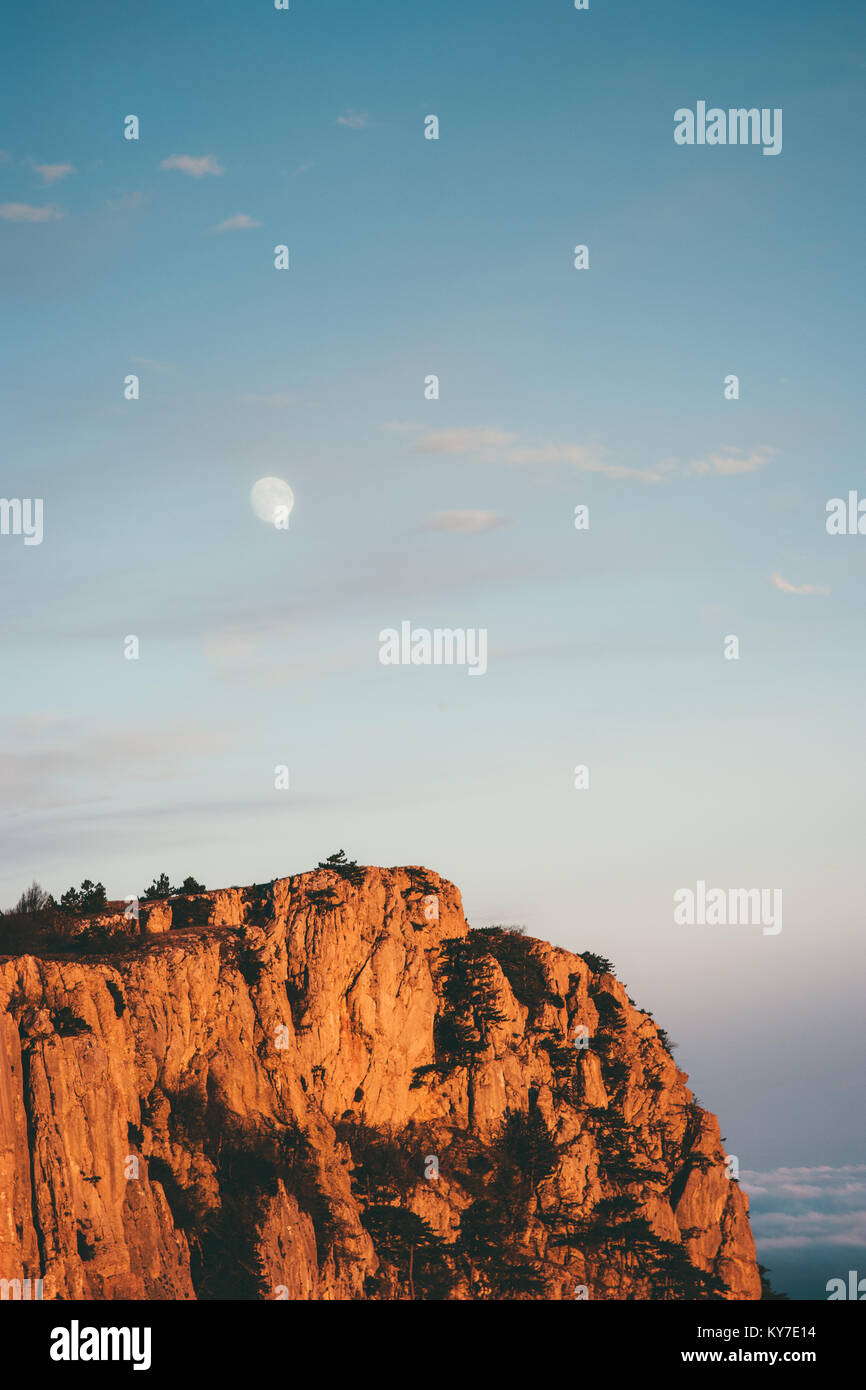 Rocky Mountains cliff and moon sunset Landscape Travel aerial view serene scenery wild nature - Stock Image