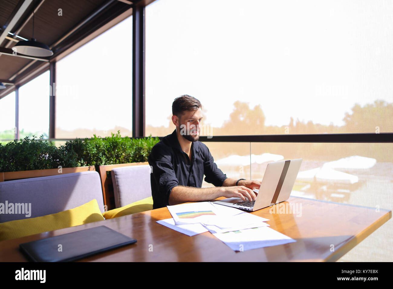Successful foreman using laptop and documents at cafe. - Stock Image