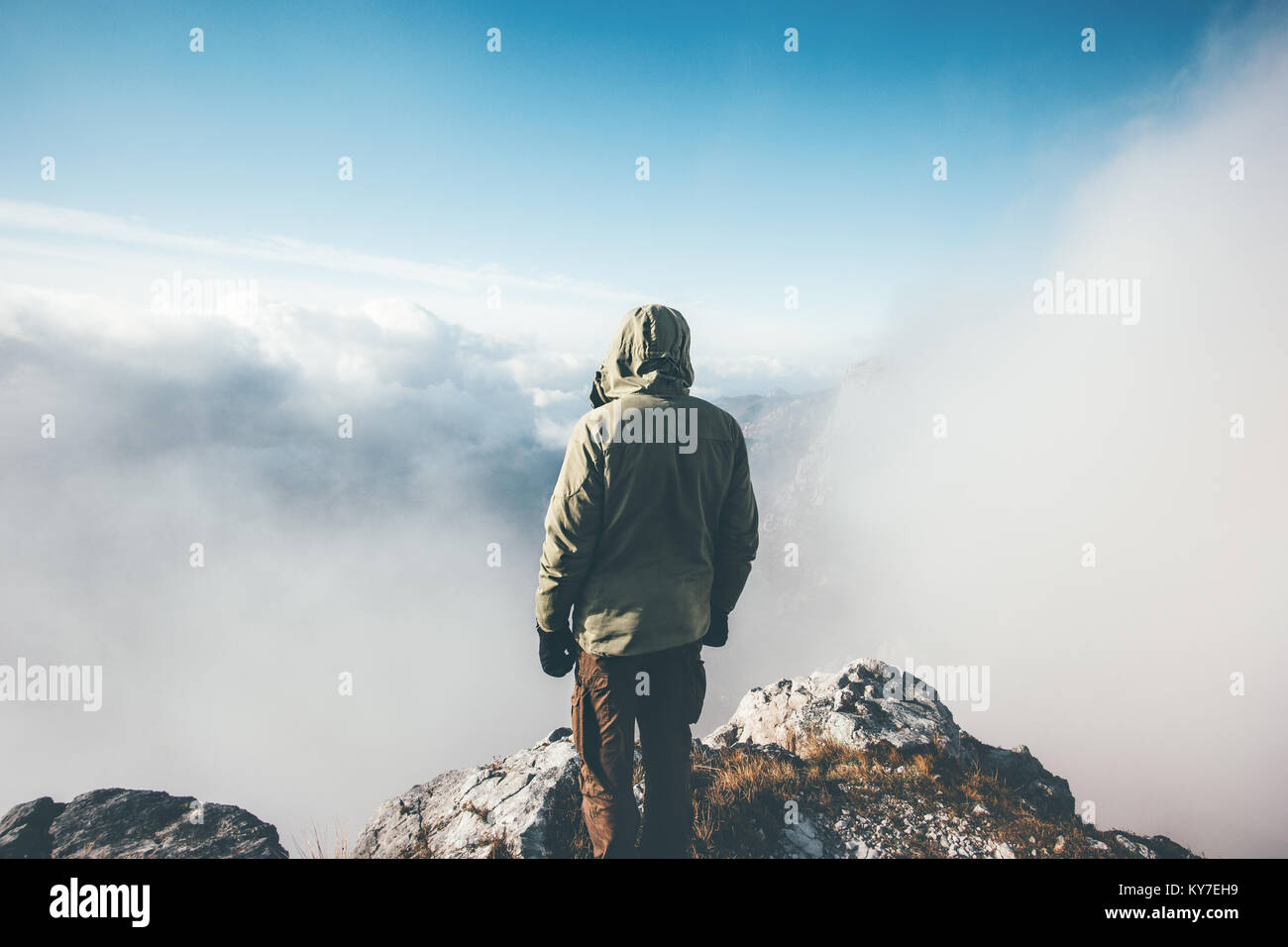 Traveler Man on mountain summit alone enjoying aerial view over clouds Travel Lifestyle success concept adventure - Stock Image