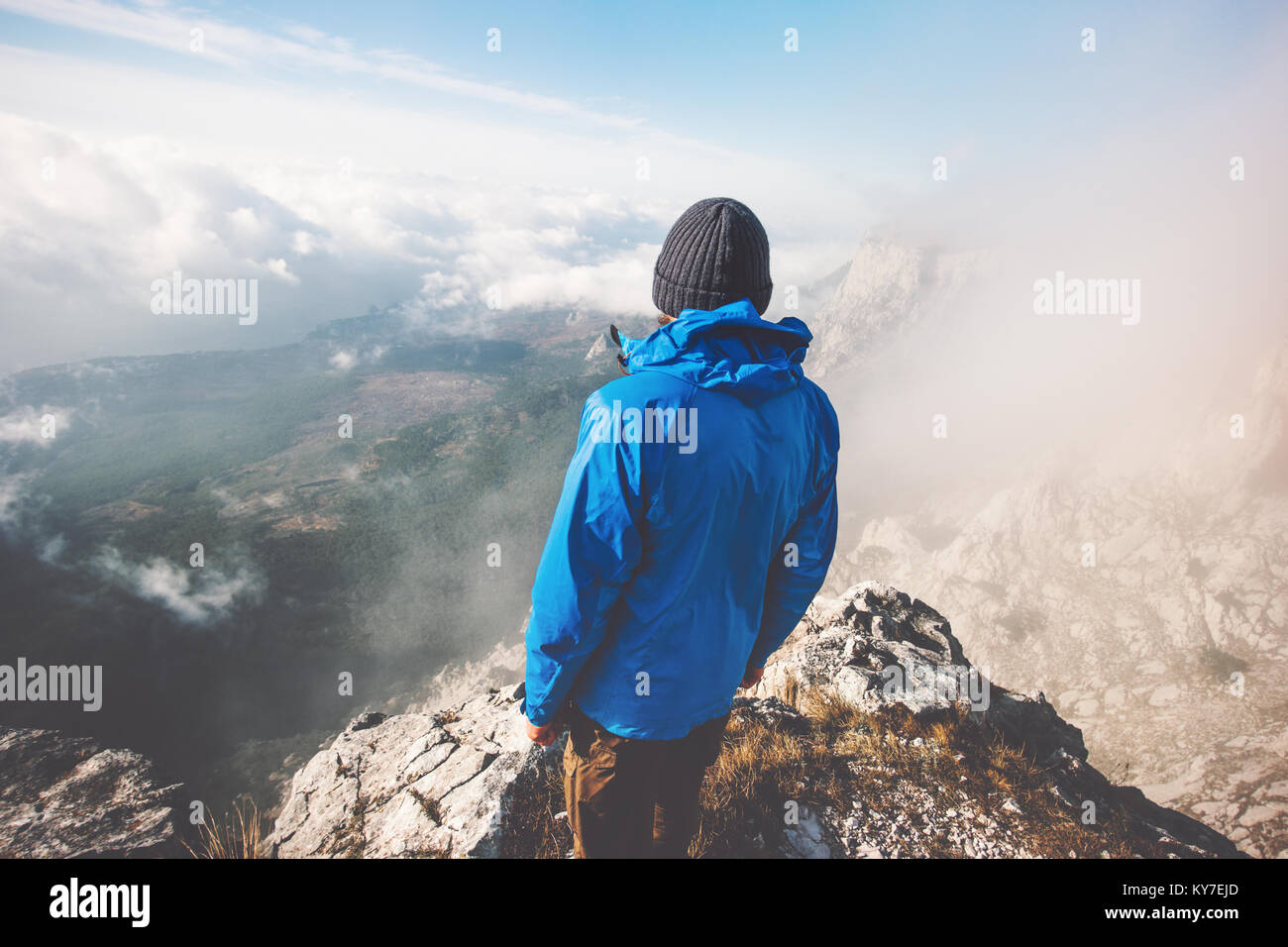 Traveler man alone on mountain summit over clouds Travel Lifestyle success concept adventure active vacations outdoor - Stock Image