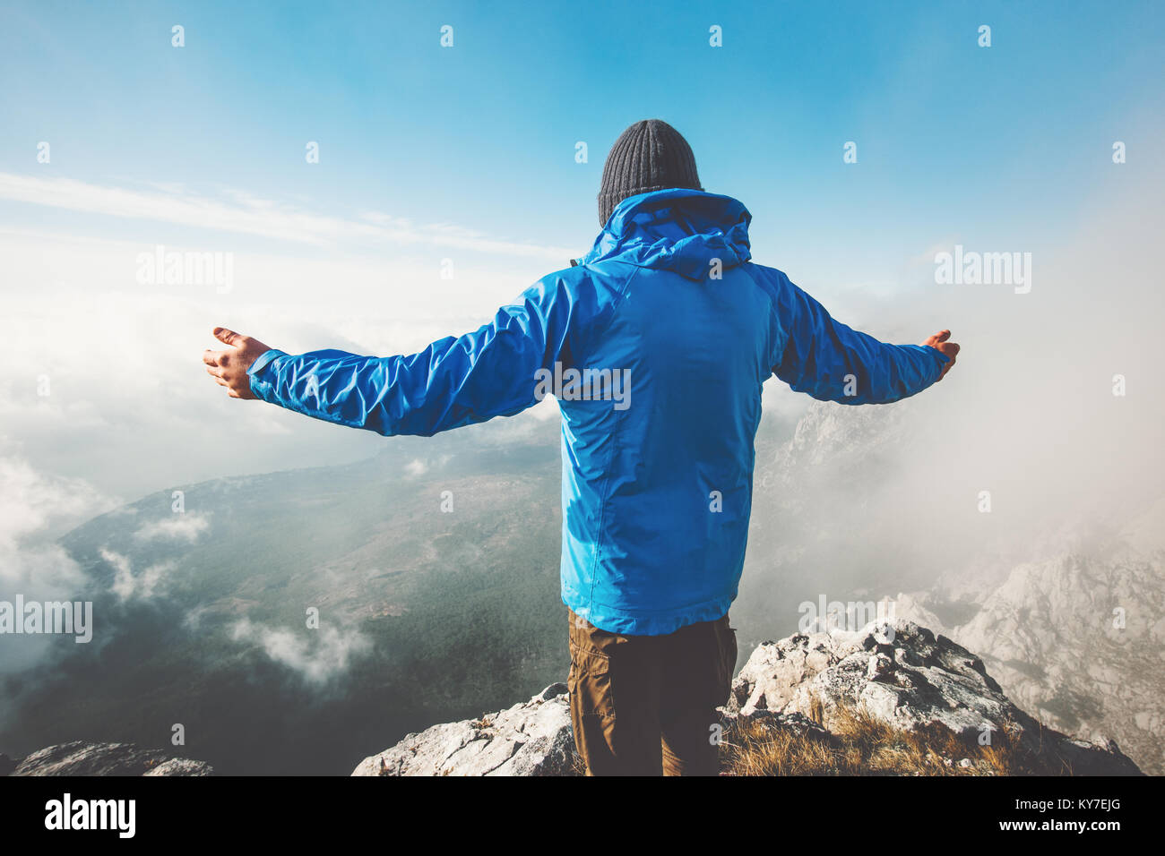 Traveler on mountain summit enjoying aerial view hands raised over clouds Travel Lifestyle success concept adventure - Stock Image