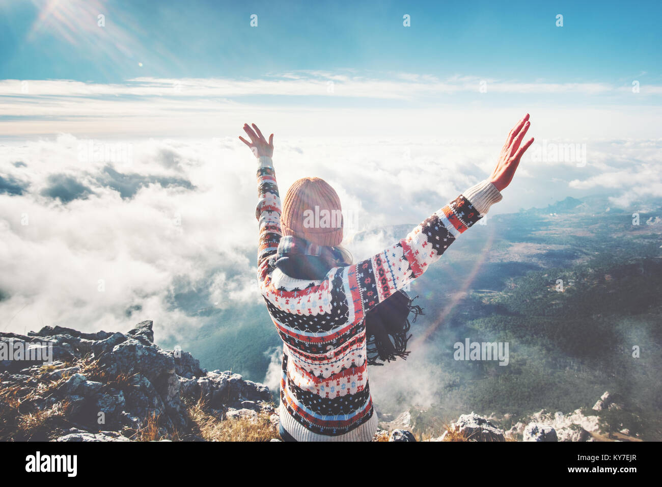 Happy girl on mountain summit hands raised over clouds Travel Lifestyle success concept adventure active vacations - Stock Image