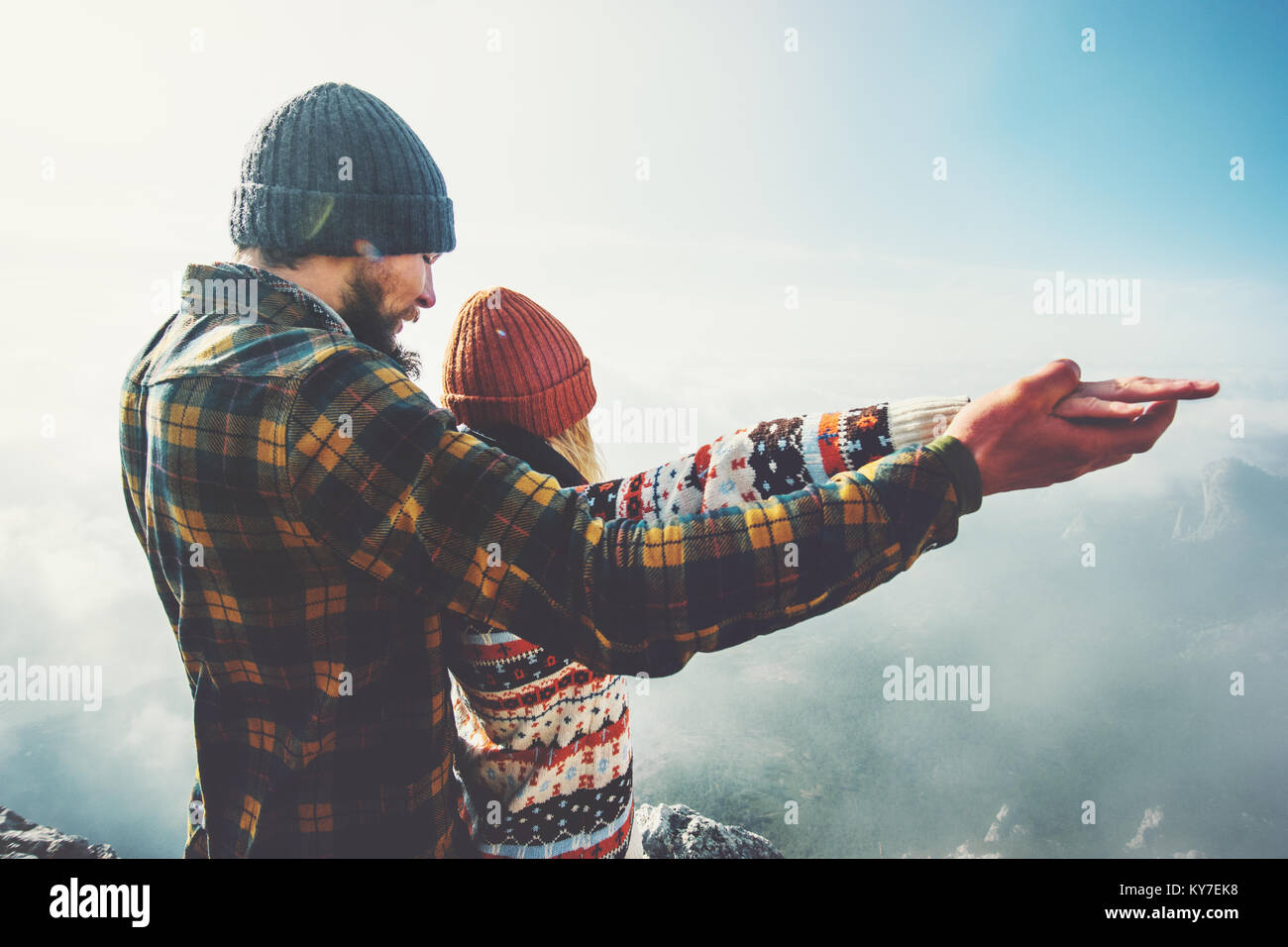 Couple Man and Woman holding hands raised together on mountain summit Love and Travel happy emotions feelings Lifestyle - Stock Image