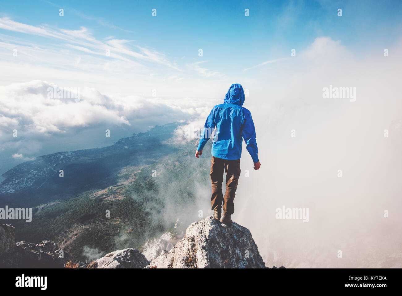 Man Traveler on mountain cliff enjoying aerial view over clouds Travel Lifestyle success concept adventure active - Stock Image