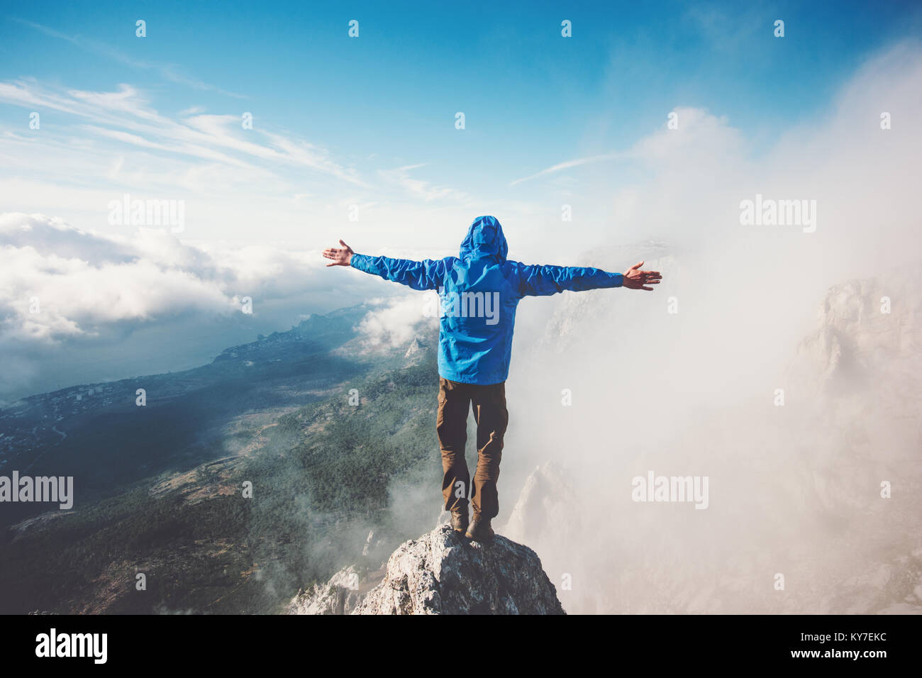 Happy Man on mountain summit enjoying aerial view hands raised over clouds Travel Lifestyle success concept adventure - Stock Image