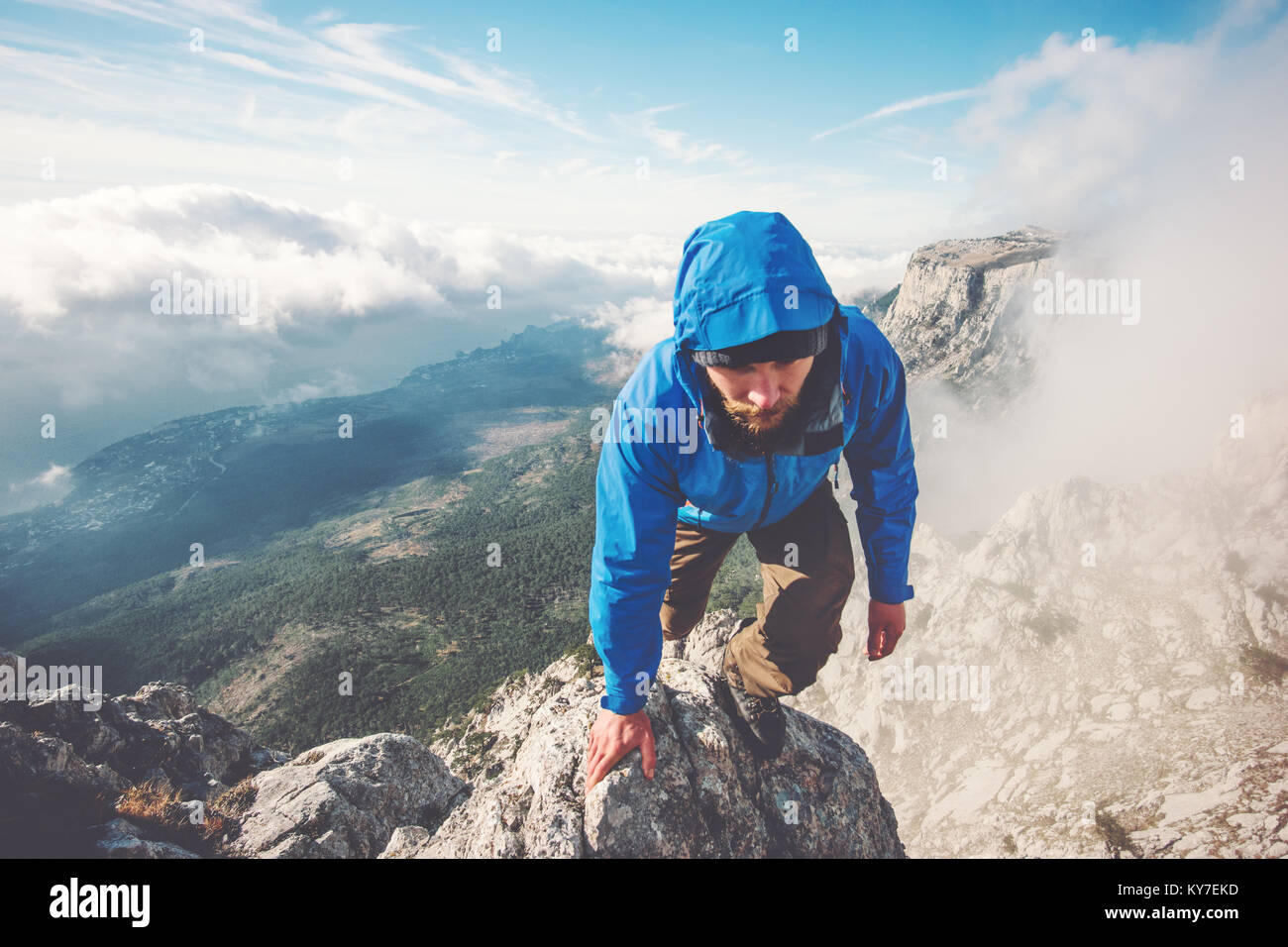 Man Traveler climbing on mountain summit over clouds Travel Lifestyle success concept adventure active vacations - Stock Image