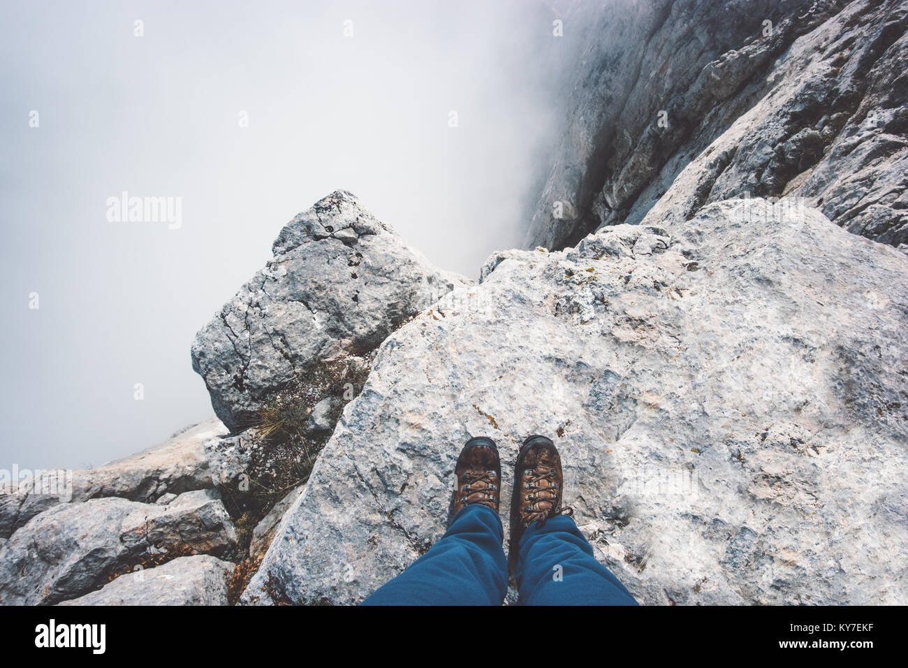 Traveler Feet boots on rocky mountain cliff over foggy clouds Travel Lifestyle success concept adventure active - Stock Image