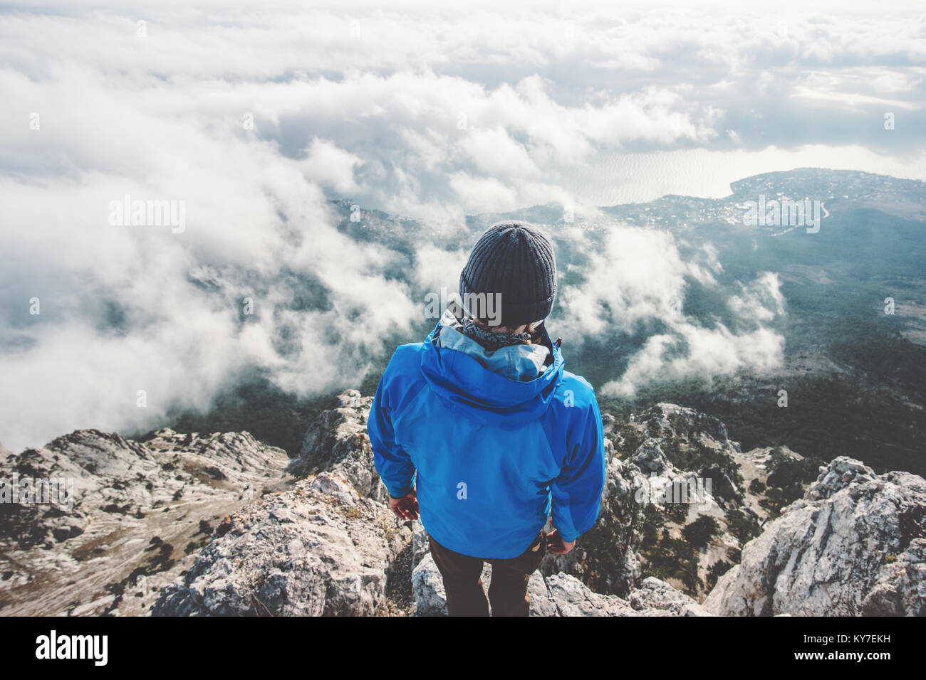 Man on mountain cliff enjoying aerial view over clouds alone Travel Lifestyle concept adventure active vacations - Stock Image