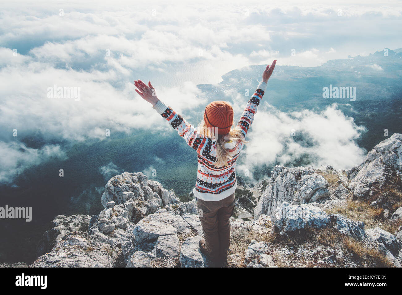 Happy woman traveler on mountain summit hands raised over clouds Travel Lifestyle success concept adventure active - Stock Image
