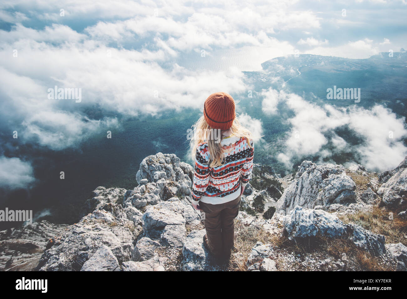 Woman traveler on mountain summit over clouds enjoying aerial view Travel Lifestyle success concept adventure active Stock Photo