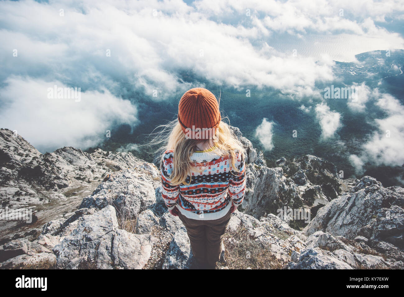 Woman traveler on mountain summit over clouds Travel Lifestyle success concept adventure active vacations outdoor Stock Photo