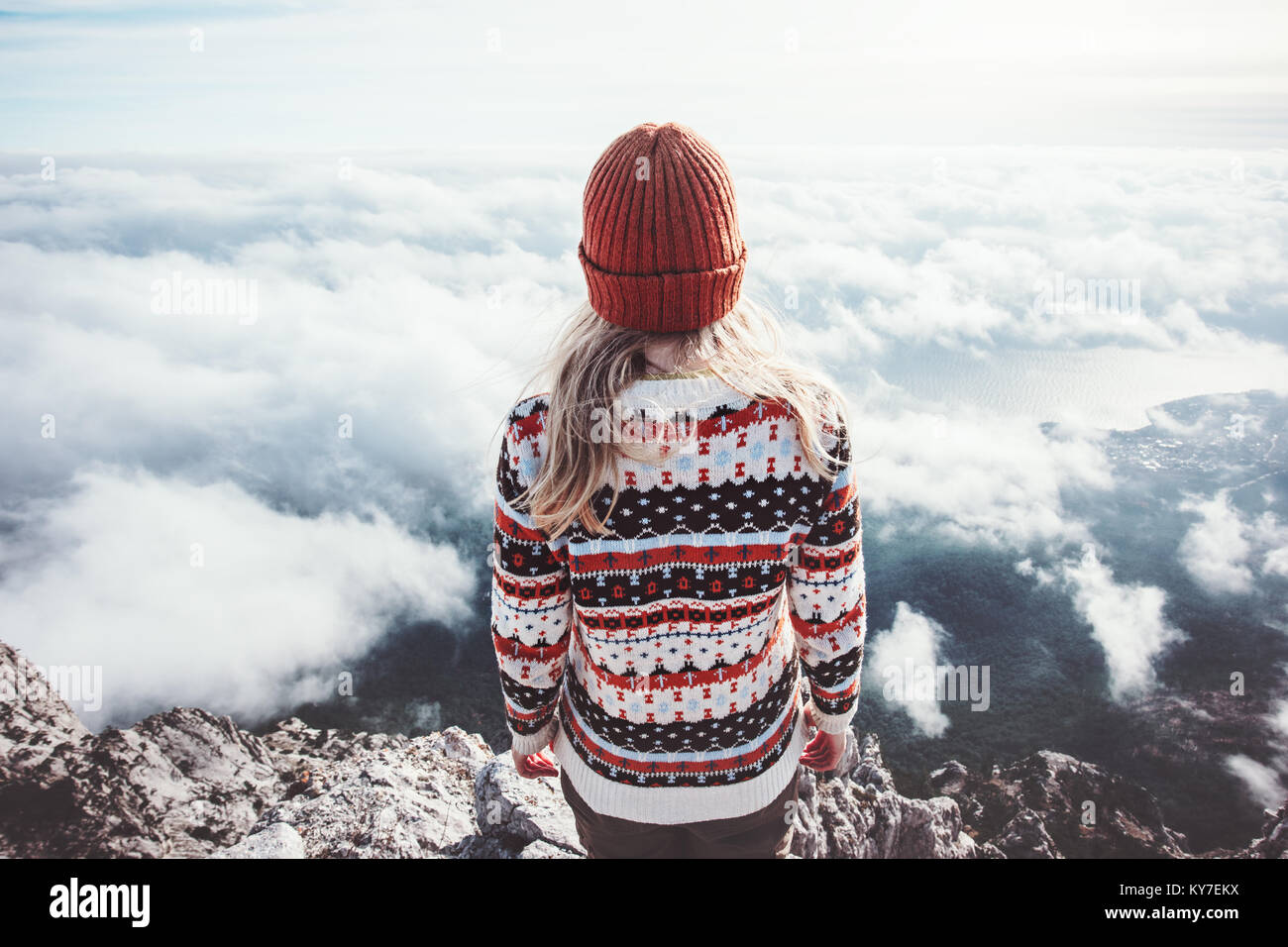 Woman traveler standing on mountain summit over clouds enjoying aerial view Travel Lifestyle success concept adventure - Stock Image