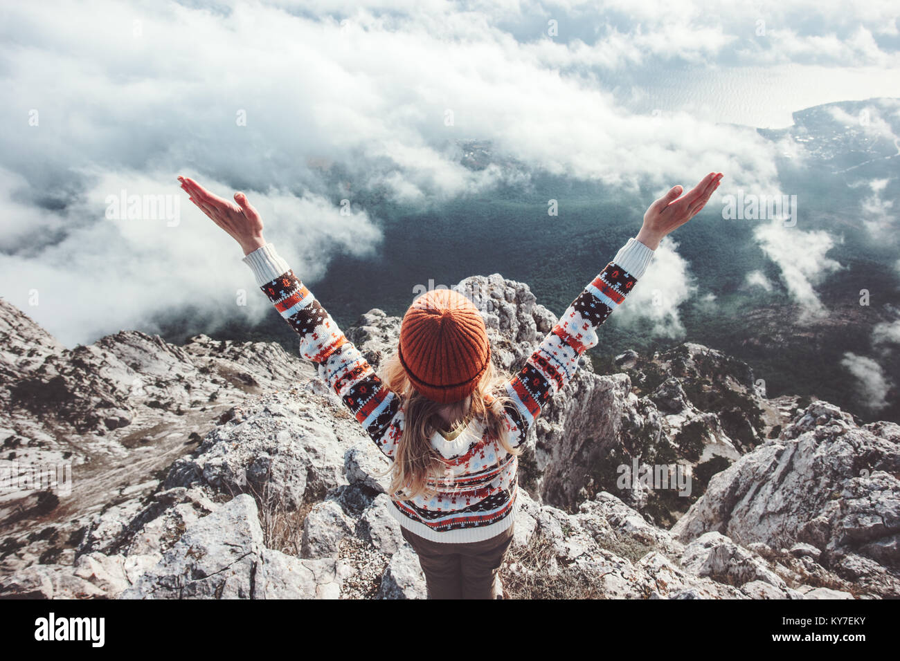Happy woman traveler on mountain summit hands raised up Travel Lifestyle success concept adventure active vacations - Stock Image