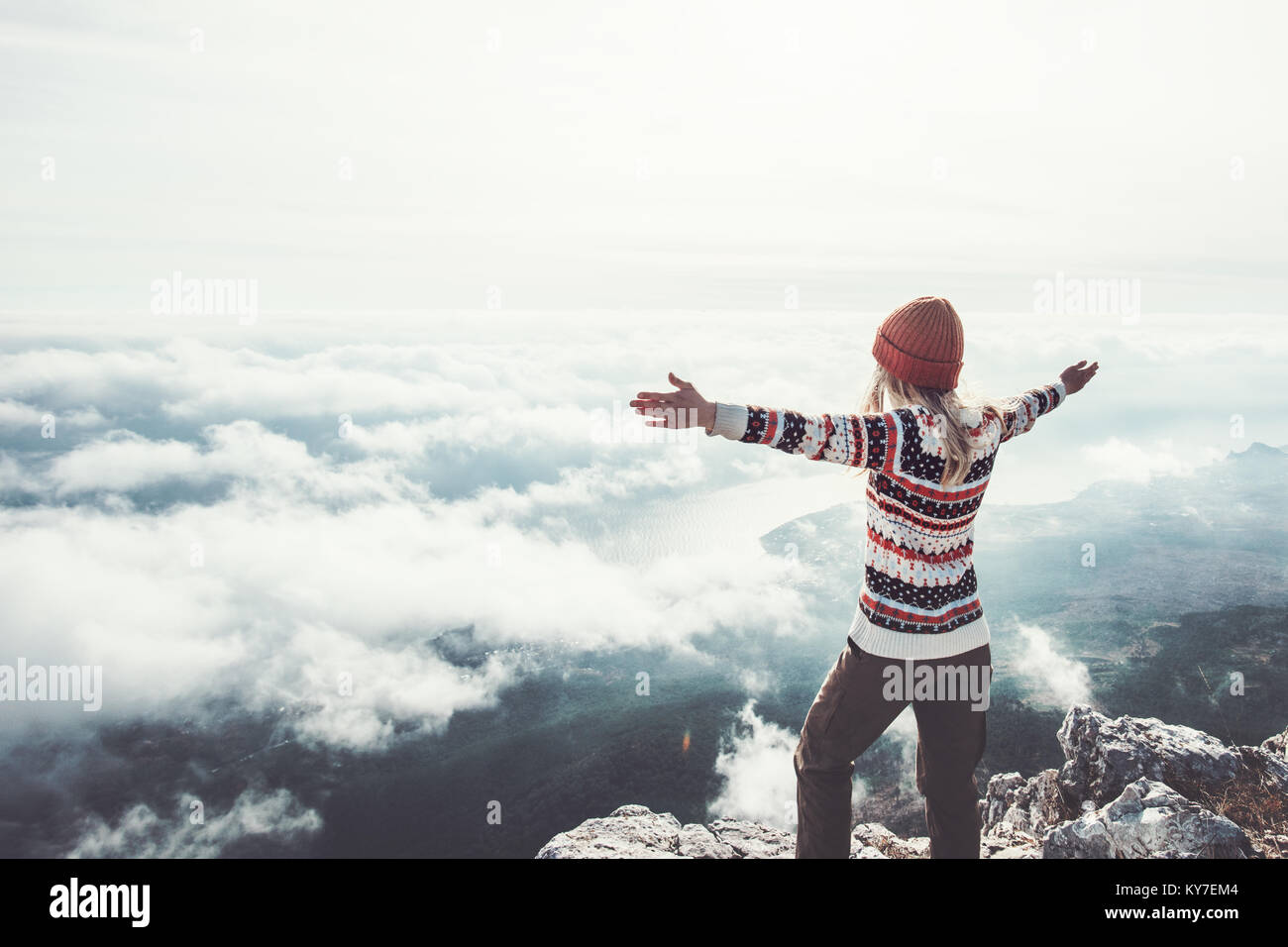 Happy woman traveler on mountain summit hands raised Travel Lifestyle success concept adventure active vacations - Stock Image