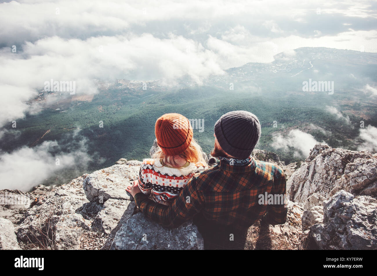 Couple Man and Woman sitting hugging on cliff enjoying mountains and clouds landscape Love and Travel happy emotions - Stock Image
