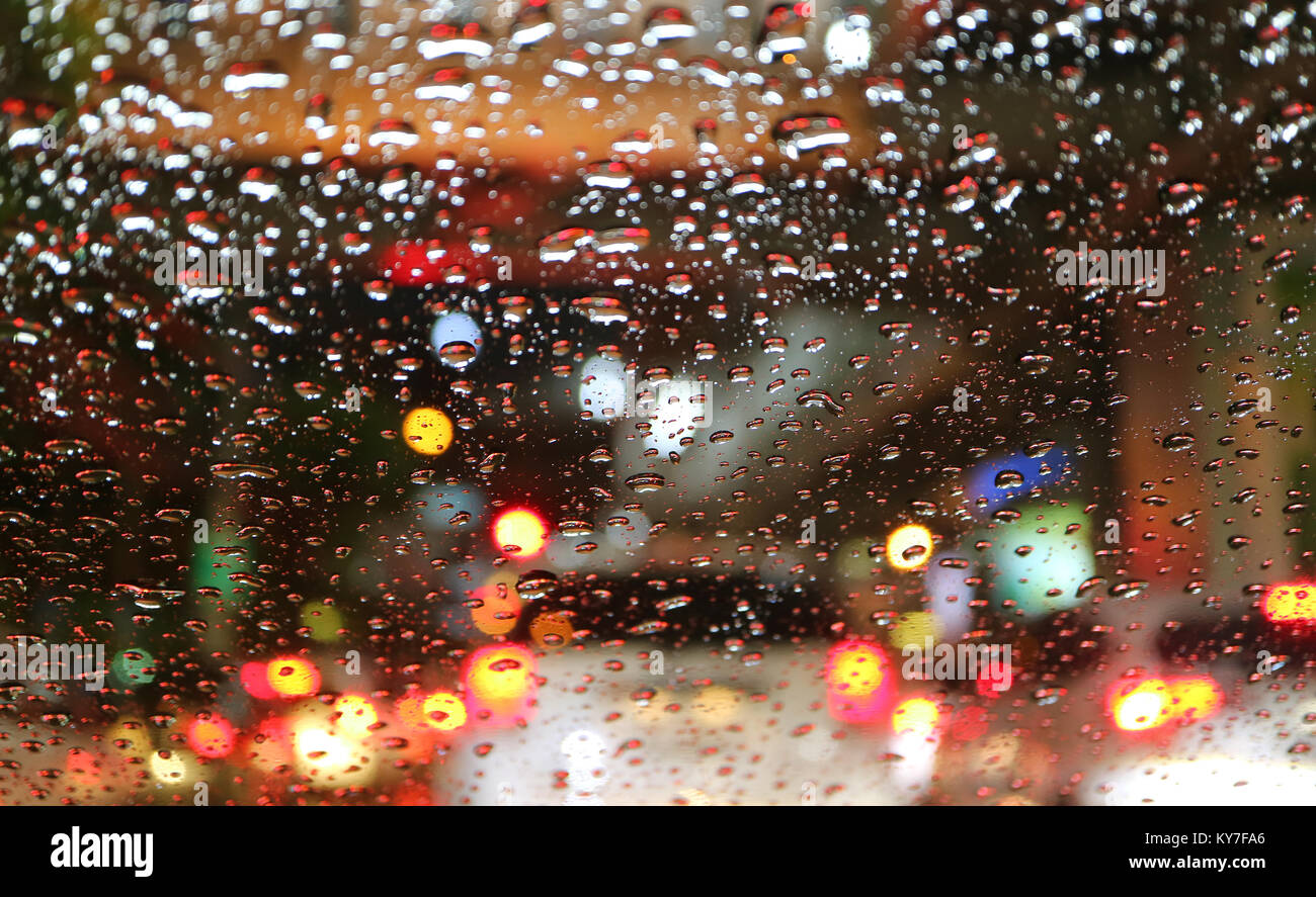 Blurred street lights and tail lamps viewed through water droplets on car windshield, for background or banner - Stock Image