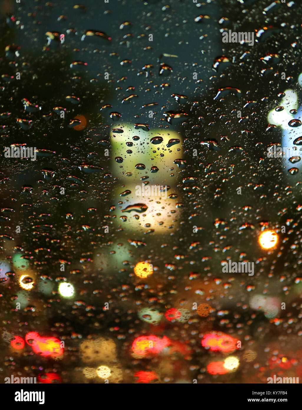 Closed up raindrops on the car windshield during a driving on the urban street at night - Stock Image