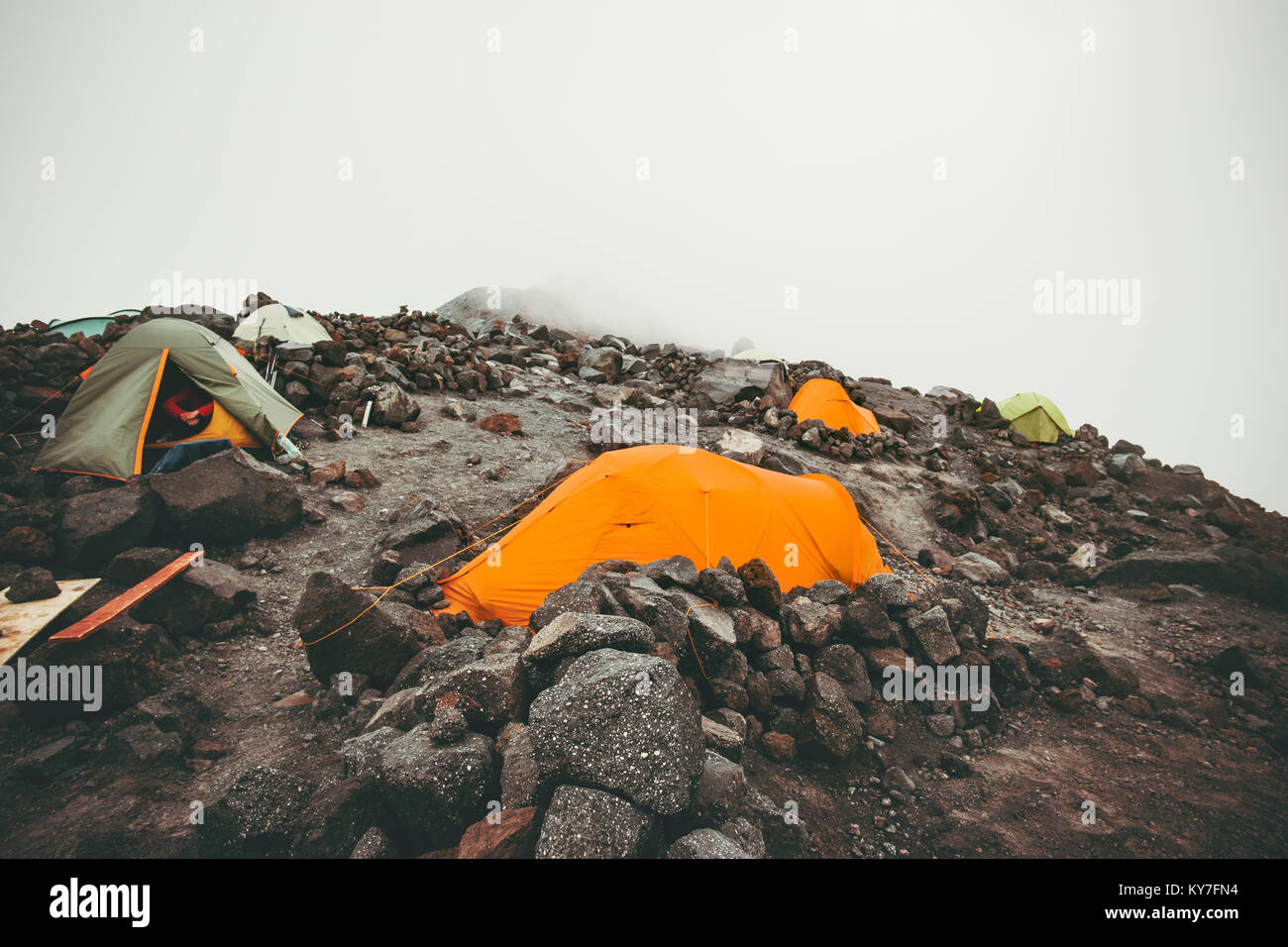 Camping tents in foggy Mountains Landscape Travel Lifestyle concept Summer adventure vacations outdoor - Stock Image