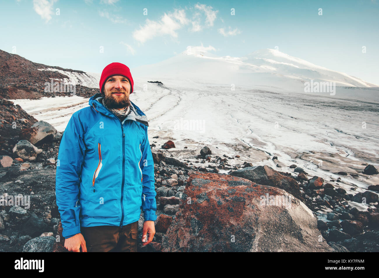 Bearded Man traveler happy smiling with Elbrus mountain on background Travel Lifestyle concept adventure active - Stock Image