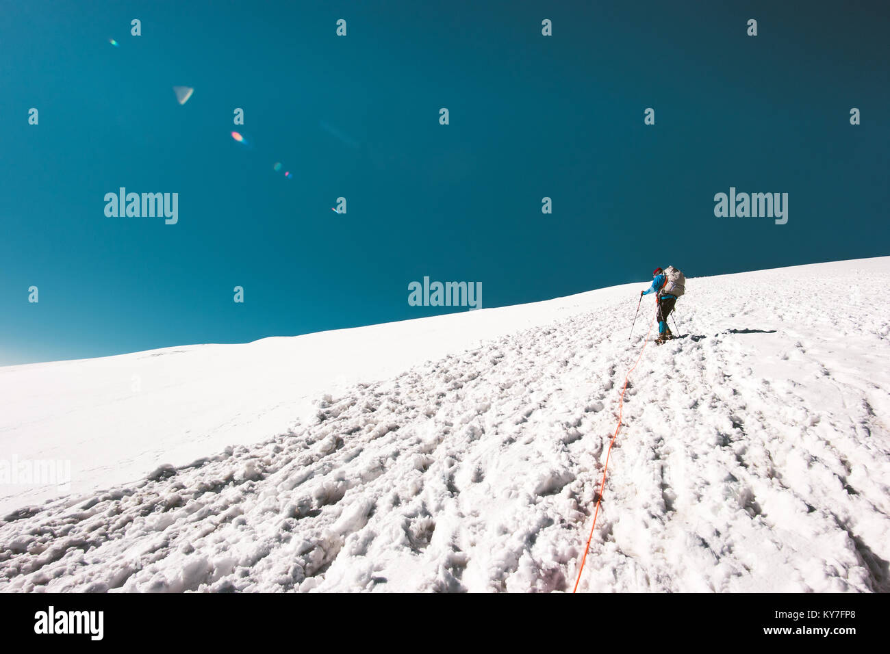 Man climbing to mountain summit on glacier Travel Lifestyle concept adventure active vacations outdoor mountaineering - Stock Image