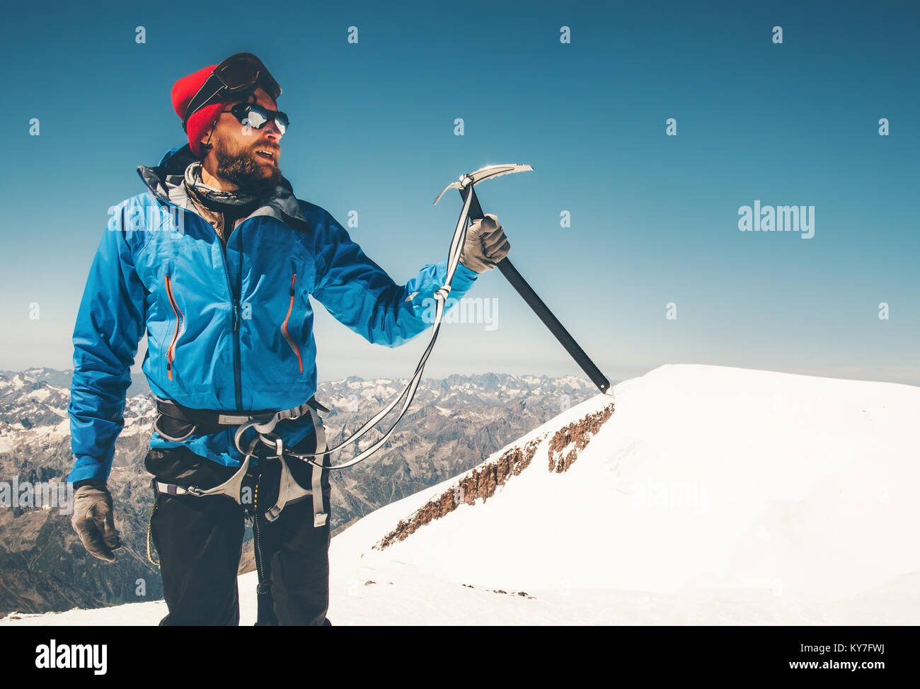 Man climber holding ice axe on mountain glacier Travel Lifestyle concept adventure active vacations extreme outdoor - Stock Image
