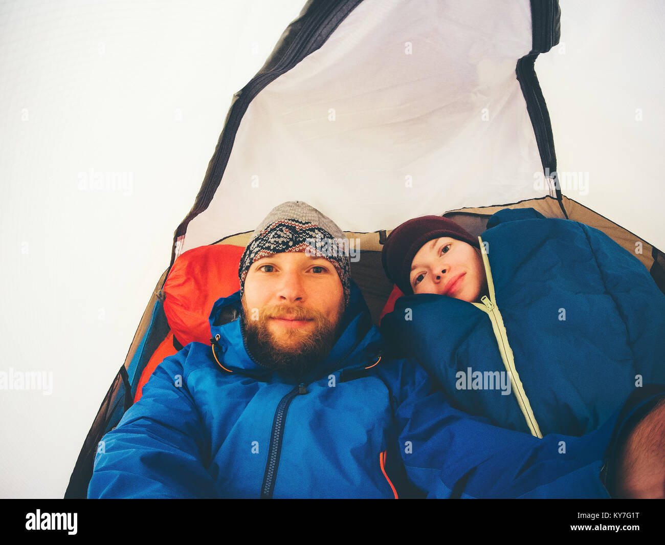 Couple travelers family Man and Woman taking selfie inside tent camping girl in sleeping bag tourism hiking equipment - Stock Image