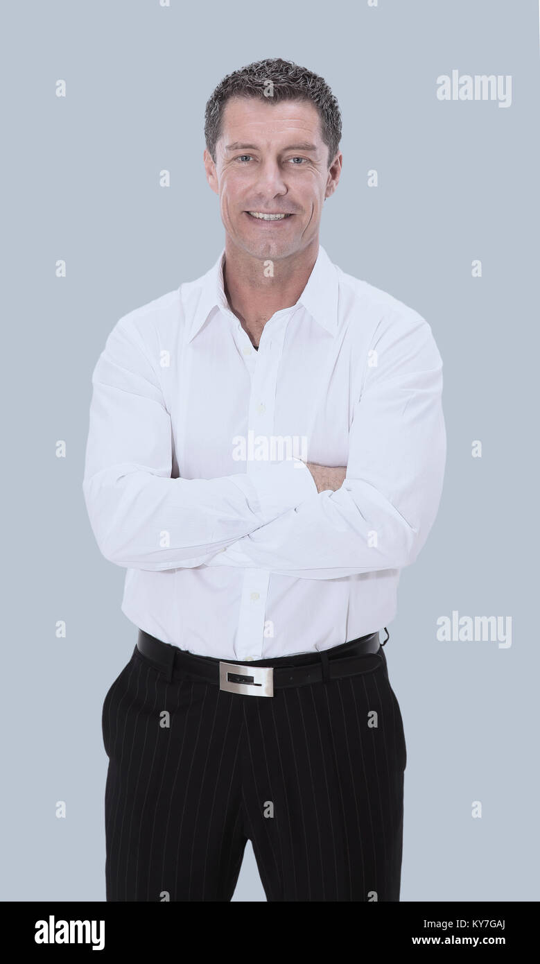 Happy mature man in shirt smiling while standing against gray - Stock Image