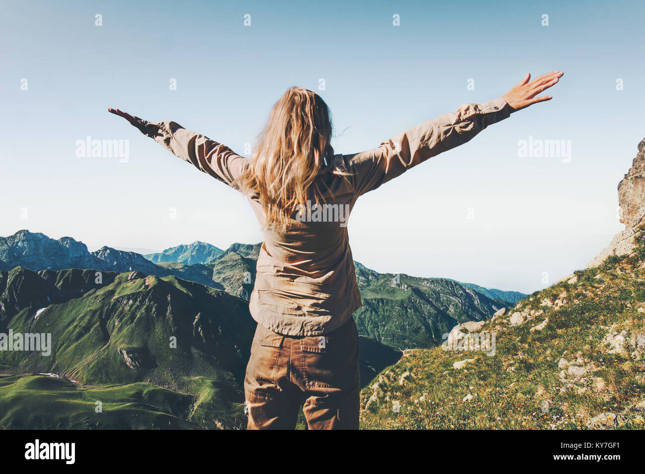 Happy Woman traveler over mountains raised hands Travel Lifestyle success and adventure concept summer vacations - Stock Image