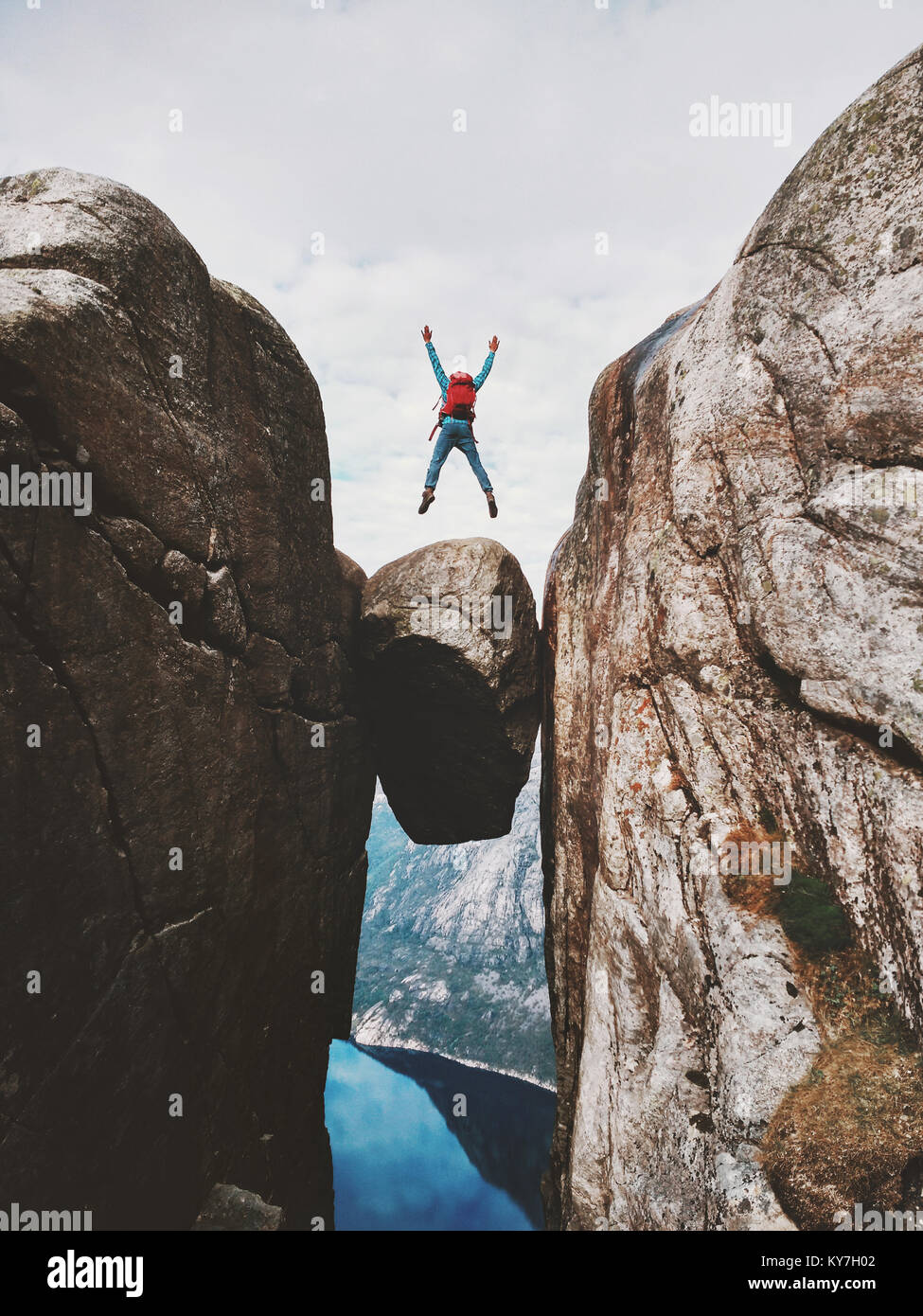 Man jumping over Kjeragbolten Travel in Norway Kjerag mountains extreme vacations adventure tourist happy emotions - Stock Image
