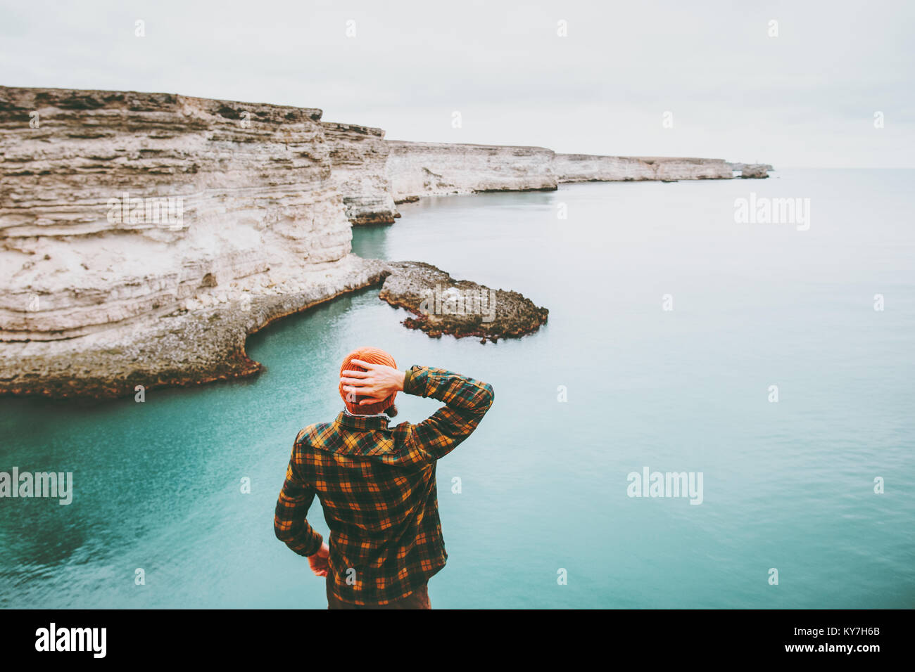 Man walking at cold sea Travel Fashion Lifestyle hat and cozy shirt clothing harmony with nature authentic style - Stock Image