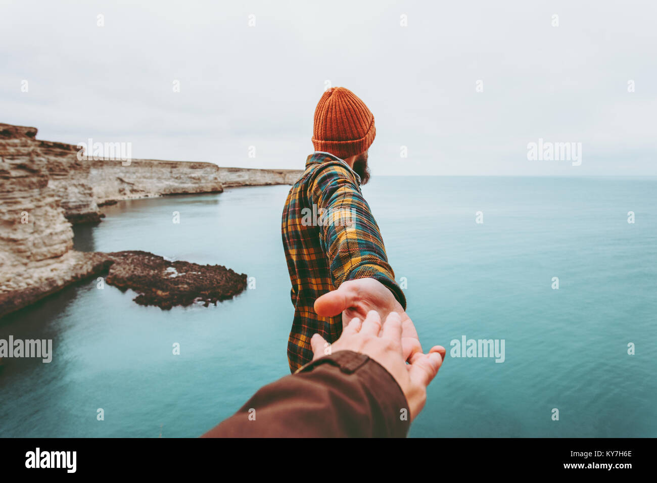 Couple Man and Woman holding hands follow enjoying cold sea landscape on background Love and Travel emotions Lifestyle - Stock Image