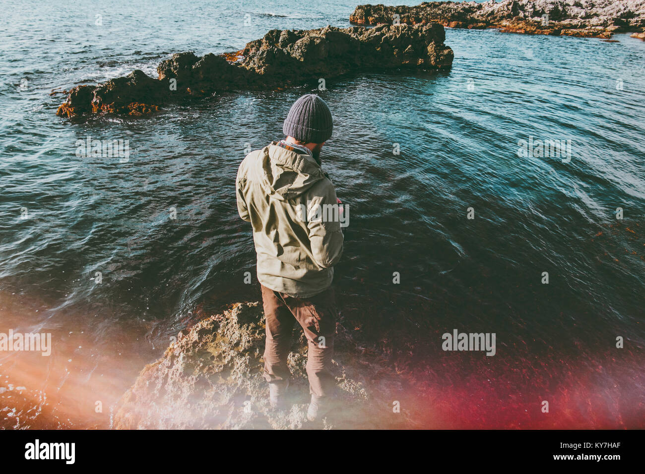 Man traveler walking at cold sea alone Travel Lifestyle concept adventure vacations outdoor natural sun lighting - Stock Image
