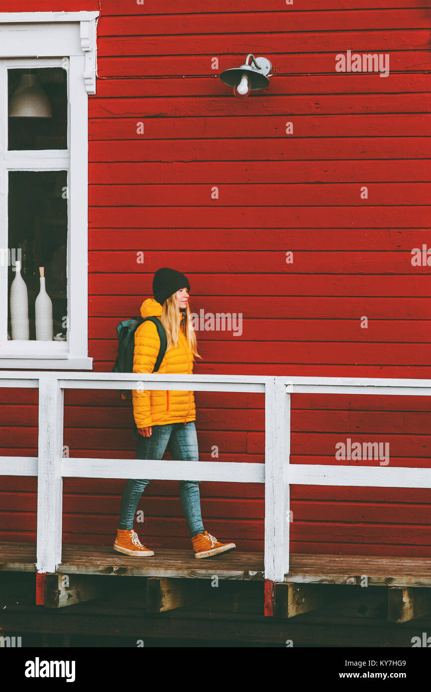 Traveler woman walking in Norway village red house wall on background Travel Lifestyle concept winter vacations Stock Photo